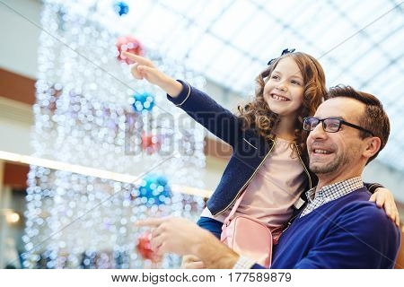 Girl held by father pointing at something in shopping-center