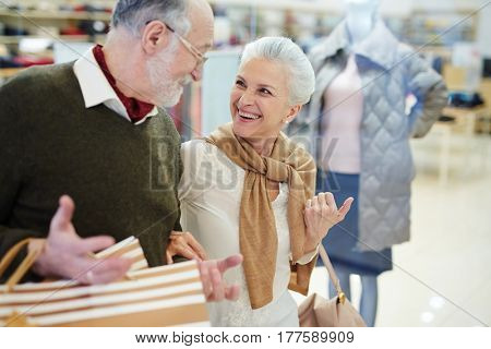 Retired man and woman laughing while passing by shop-window