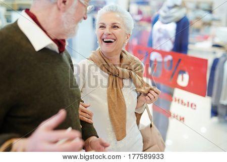 Laughing senior female talking to her husband during shopping