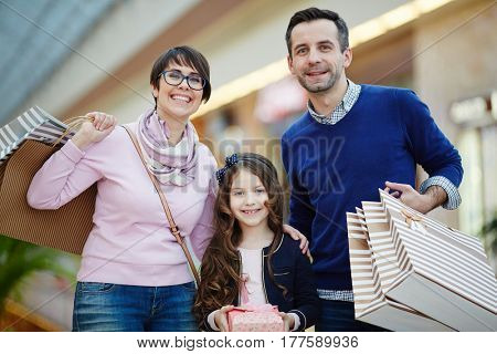 Young family of three spending time in shopping center