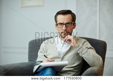 Portrait of handsome middle-aged psychologist in eyeglasses looking at camera while sitting on comfortable armchair and filling in medical card