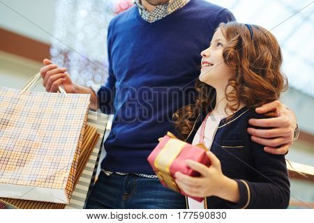 Adorable girl with packed present looking at her father during shopping