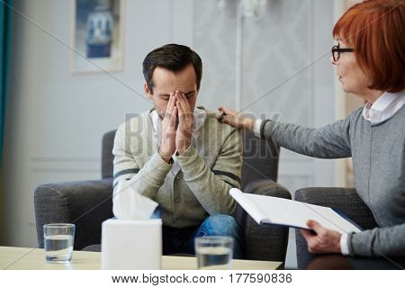 Upset middle-aged patient covering face with hands while sitting on cozy armchair, his mature psychologist trying to comfort him
