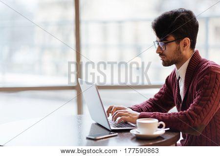 Mobile businessman or freelancer networking in cafe