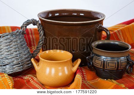 Ceramic mugs on decorative tablecloth. Retro objects.