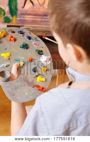 Process of mixing colors. Attentive gifted involved child sitting in the art studio and having art class while holding pallet and mixing colors