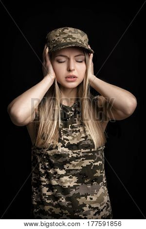 portrait of a beautiful blond woman soldiers in military attire closes his ears with his hands on black background