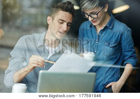Informal business meeting in coffeehouse: young handsome man sitting at table and discussing new contract terms with his business partner before signing it, view through window