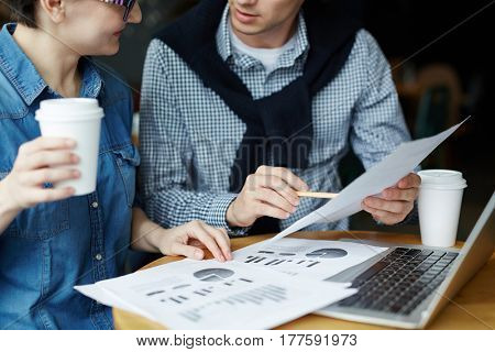 Close-up shot of small round table with business documents, laptop and paper cup of coffee, two young coworkers sitting next to each other and wrapped up in work