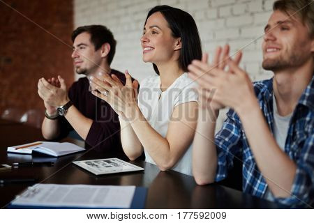 Happy business people applauding to speaker at conference