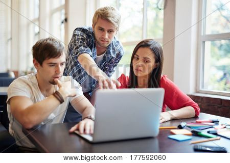 Three business people looking at data on laptop screen