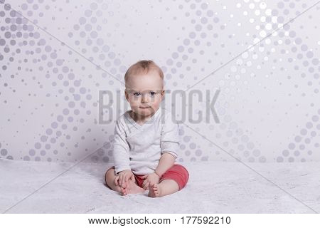 Cute little toddler sitting on grey tblanket. Copy space. Horizontal indoor shot