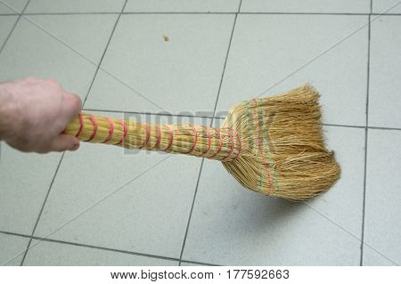 Brooms on the floor covered with tile