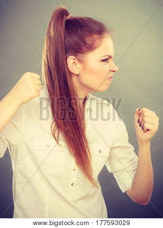 Negative emotions. Angry mad woman clenching fist punching on gray.