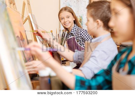 Full of joy. Laughing upbeat delighted children sitting in school and having painting class while practicing their skills and expressing happiness