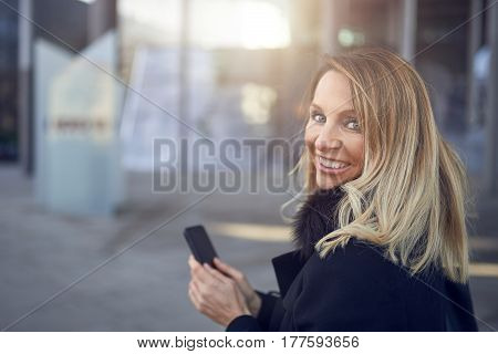 Smiling attractive woman looking back over her shoulder as she stands in a street in town holding a mobile phone with copy space