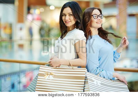 Attractive girls with paperbags spending weekend in the mall
