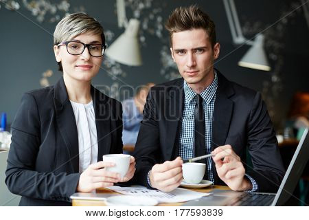 Male and female manages posing for photography while drinking coffee in small cafe and working on their joint project, waist-up portrait