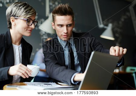 Teamwork in lovely coffeehouse: pretty young businesswoman holding cup of coffee and looking at computer screen, while her male colleague showing her project