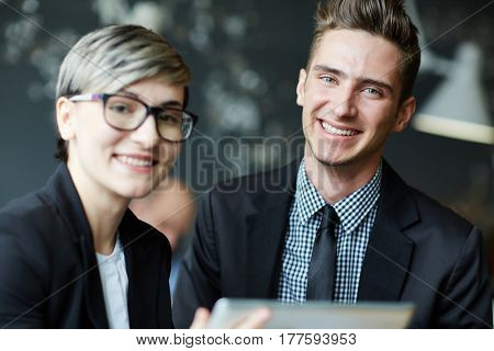 Pretty young businesswoman in stylish eyeglasses and her handsome colleague distracted from project discussion and posing for photography with toothy smiles