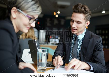 Two young business partners sitting in coffeehouse and discussing details of contract, waist-up portrait