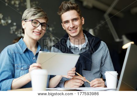 Low angle view of two colleagues sitting in small cozy cafe and looking at camera with wide smiles, paper cups of coffee and laptop standing on table