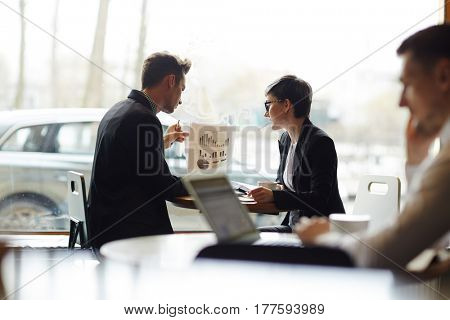 Busy employees in formalwear sitting at cafe window and analyzing statistics, stylish businessman holding document with financial diagrams