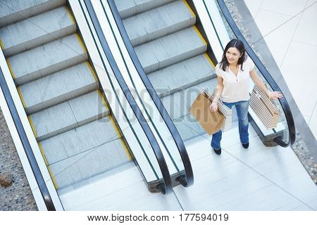 Shopper with bags standing by escalator in the mall