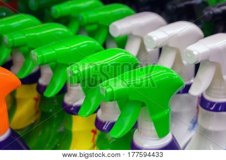 Close up of colorful spray bottles with cleaning agents in supermarket