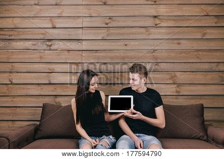stylish man and woman sitting in bed room and hold tablet pad computer. looking at them and show empty touch screen with copy space