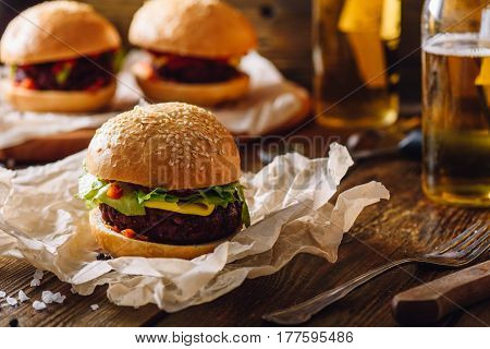 Cheeseburger on Kraft Paper and Some Burgers with Bottles of Beer on Background.