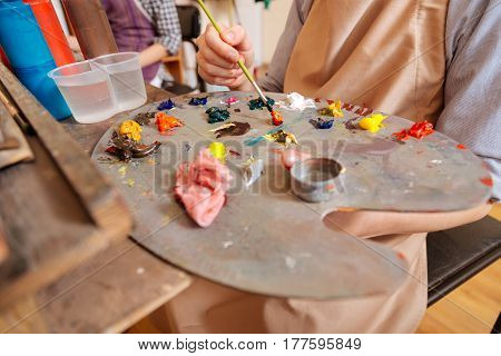 Mixing colors . Pleasant skillful gifted child sitting at school and painting while using paintbrush and pallet
