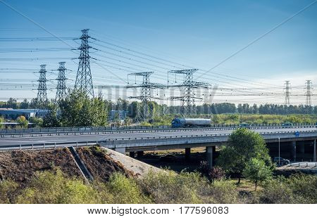 Beijing, China - Oct 31, 2016: Power poles and modern highway marking the countryside soon after leaving Beijing city. Captured from within a High-Speed Rail (HSR) bullet train traveling at 300 km/h.