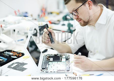Side view portrait of man opening disassembled computer and using flashlight to inspect broken parts in circuit board at table in workshop