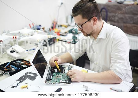 Portrait of modern man wearing glasses busy with electronics in workshop: disassembling laptop and reconstructing it with different tools and parts on table