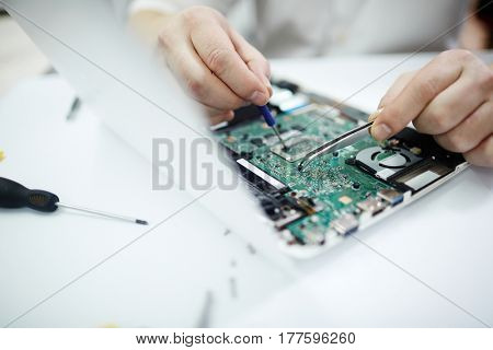 Closeup shot of male hands repairing parts in disassembled laptop using screwdriver and different tools on table in workshop