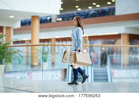 Happy girl moving down shopping center at leisure