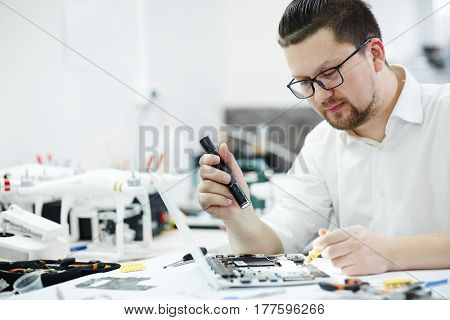 Side view portrait of man inspecting disassembled laptop with flashlight, looking for broken pats in workshop