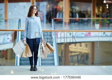 Casual shopper with paperbags standing in shopping-center