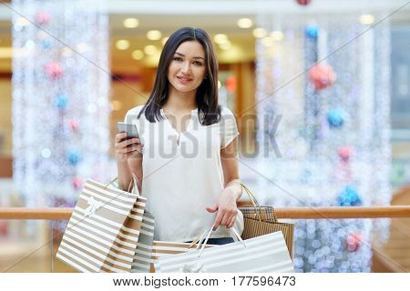 Modern shopper with cellphone and shopping bags