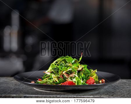 Concept of healthy food. Fresh spring green salad with lettuce, pomegranate and grapefruit, in black plate. Dark interior of modern restaurant kitchen in the background. Ready to eat.