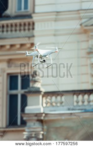 Black and white quad copter flying at the building background