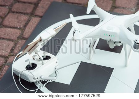 white remote controller and quad copter on the helicopter landing spot