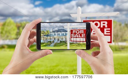 Female Hands Holding Smart Phone Displaying Photo of For Sale Real Estate Sign and House Behind.