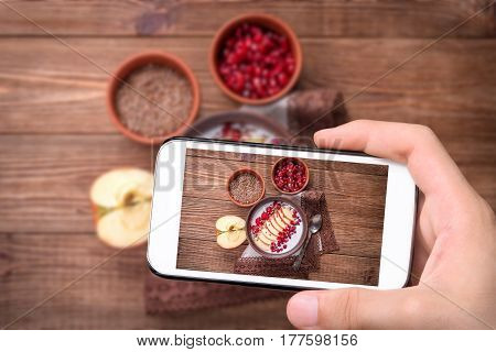 Hands taking photo yogurt with apple slices , raspberries and garnet with smartphone.