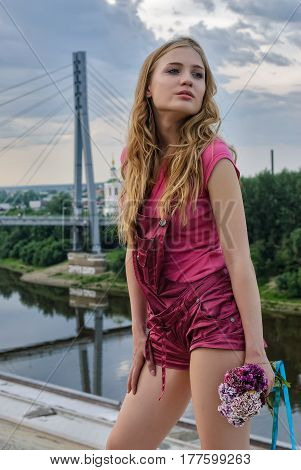 Portrait of young attractive woman with bouquet over bridge background
