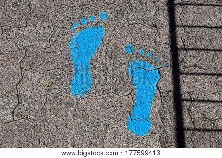 Blue footsteps drawn in playground rubber flooring
