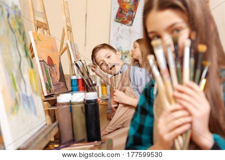 Having fun together. Playful joyful positive kids sitting in the art studio and having painting class while expressing joy and holding paintbrushes