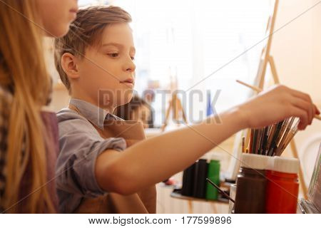Enjoying oil painting on canvas. Concentrated talented pleasant kids sitting in the studio and having painting class while painting in the interaction with each other