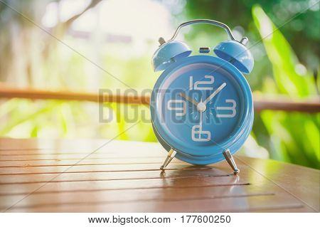 Blue alarm clock on a wooden desk with nature background, close up blue alarm clock
